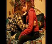 Girls kissing on the bed.