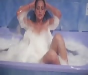 Scène softcore dans une baignoire avec une charmante brune
